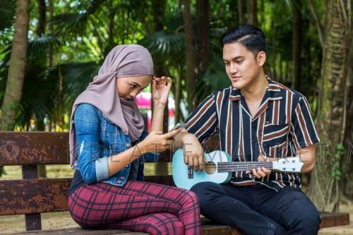 young malaysian youth man woman learning playing ukulele at park, looking at smartphone adjusting hijab
