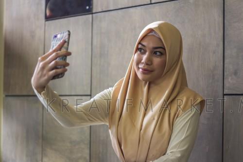 muslim hijab lady using smartphone taking photo selfie happy face