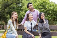 Happy Teenage friends outdoor park having fun feeling happy smiling looking away