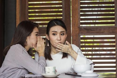 two young asian girls friends gossiping home hearing feeling shock