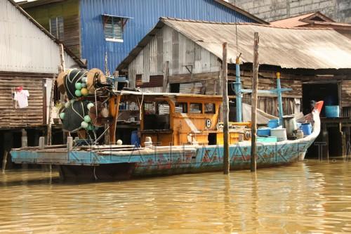 Fishing boat moored at house at Port Weld, Kuala Sepetang