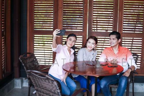Girl taking selfie wefie with friends, focus on phone