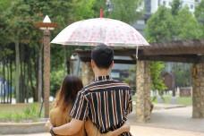 Two young youth adults walk talk express under umbrella boy girl man woman outdoor garden park