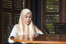 close-uo hijab malaysian muslim woman texting business partner using cell phone restaurant, meeting indoor