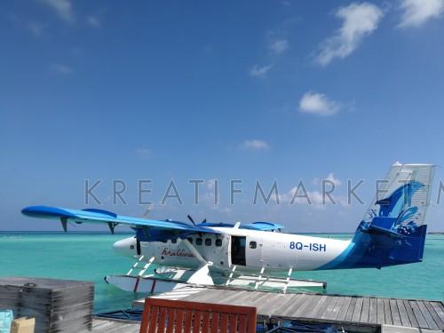 Seaplane air taxi fly over Atolls oa Maldives near Kanifushi island