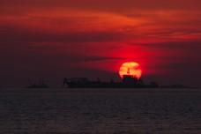 Cargo ship against setting sun